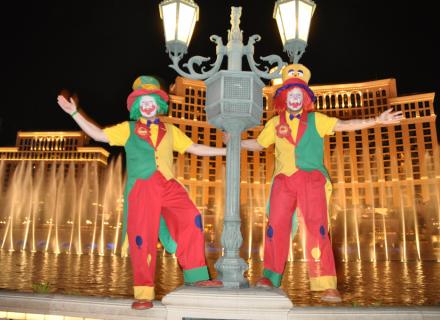Clown August & Clown Pippy halten sich an einer Laterne vor dem Bellagio Hotel fest.